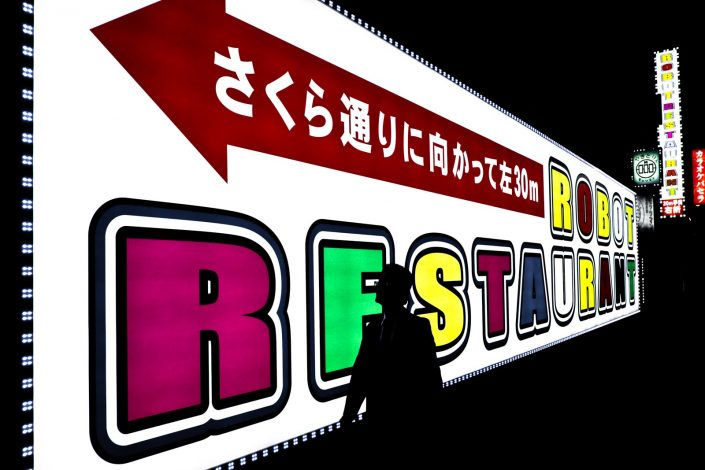 Robot Restaurant sign in Shinjuku, Tokyo. A man is walking in front of the sign.