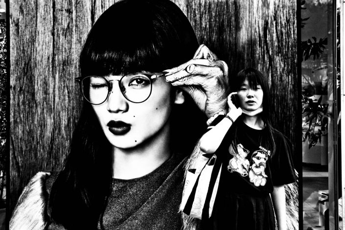 one girl on a billboard with glasses and one real girl with smartphone at Harajuku. Street Photography by Victor Borst