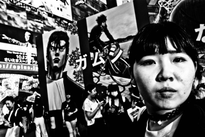 Close up of Japanese girl at Shibuya Tokyo with lots of billboards behind her. Street Photography by Victor Borst