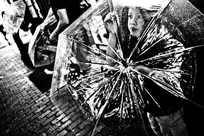 Japanese Girl in rain protecting herself with a see-through umbrella at Shibuya. Street photography by Victor Borst