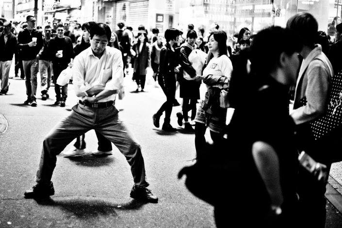Japanse man is standing still in a weird kinda way at Shibuya, Tokyo. Street photography by Victor Borst