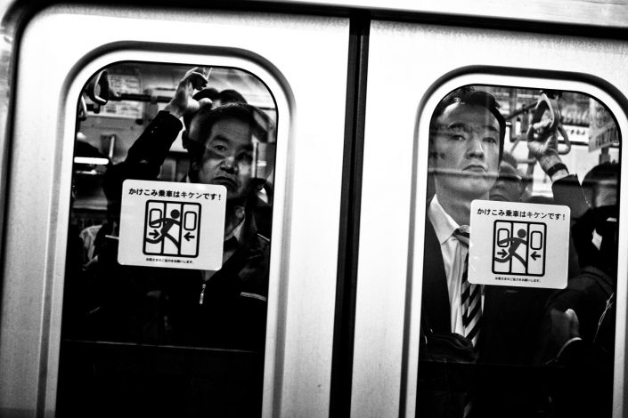 Japanese salarymen in front of metro door. Looking angry at me. Street Photography by Victor Borst