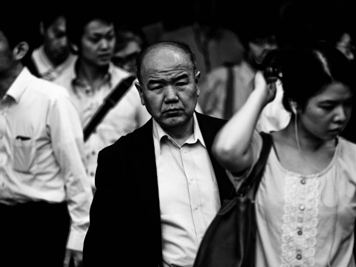 A portrait in the crowd during rush hour in the morning at Shimbashi station. Street Photography by Victor Borst