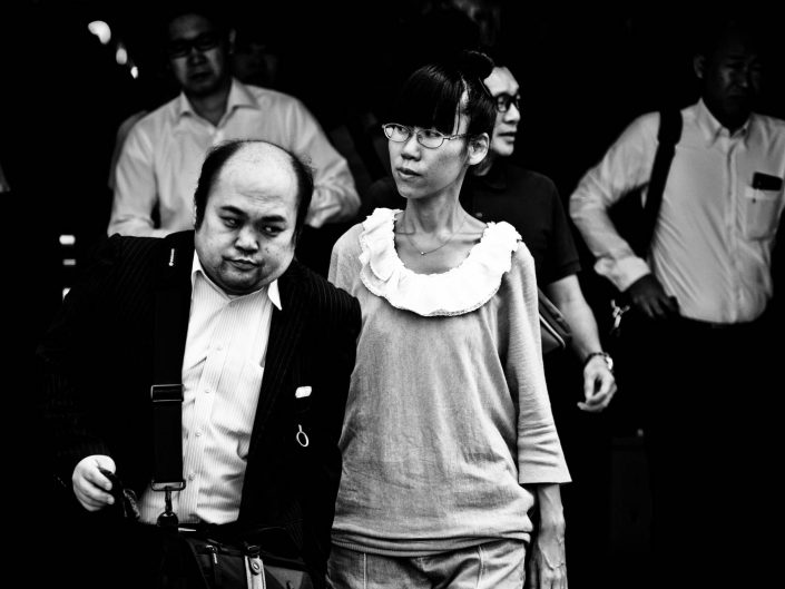 One semi-bald man and one woman with glasses going to work at Shimbashi station. Street Photography by Victor Borst