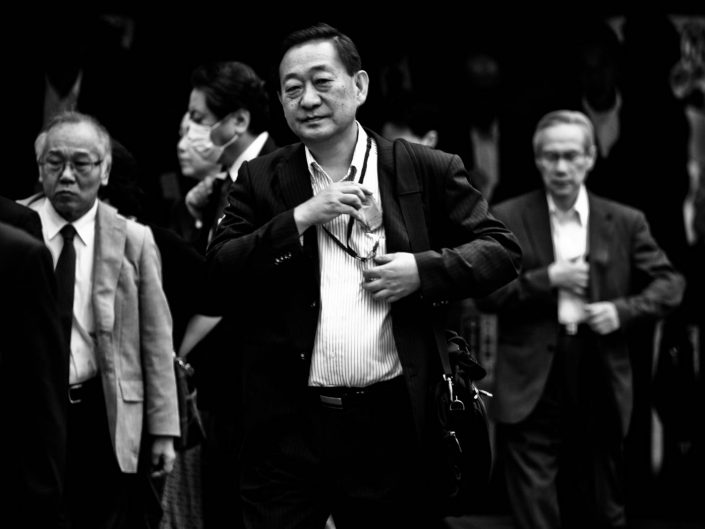 Group of salarymen at Shimbashi station with on the foreground one smiling. Street Photography by Victor Borst