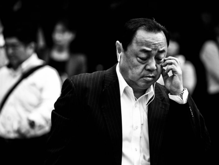 Portrait of Japanese man scratching near his eye. Street Photography by Victor Borst