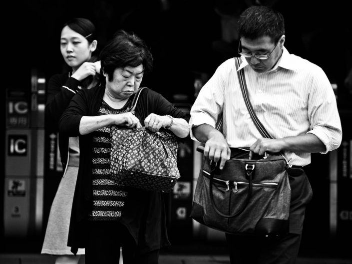 One Japanese man and woman both searching in their handbag. Street Photography by Victor Borst