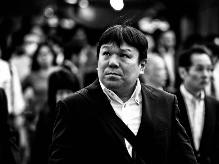 Portrait of a salaryman at Shimbashi station. he is looking up. Street Photography by Victor Borst