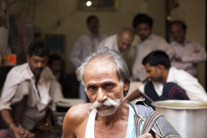 Colorful India, Indian man in the forefront with a mustache and people in dof cooking stuff. Made in Varanasi.